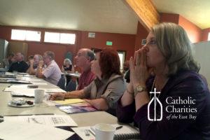 Debra Gunn (foreground) and Stephen Mullin (center) listen carefully to the presentation.